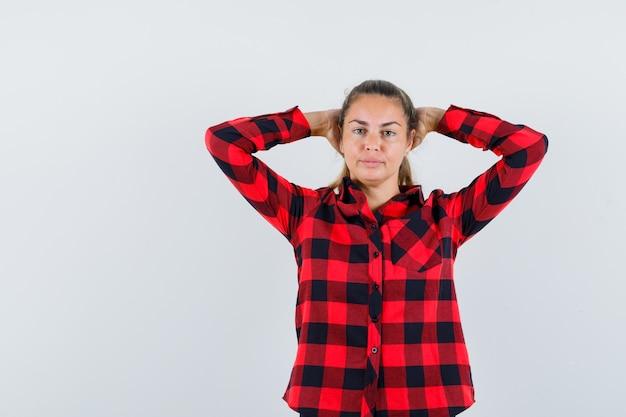 Молодая дама в клетчатой рубашке держится за руки за головой и выглядит красиво
