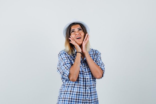 Young lady holding hands on cheeks in checked shirt hat and looking cute