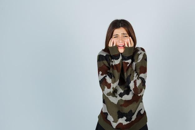 Giovane donna che tiene le mani sulle guance, piangendo in maglione e guardando triste
