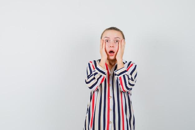 Giovane donna che tiene le mani sulle guance in camicia a righe e sembra scioccata