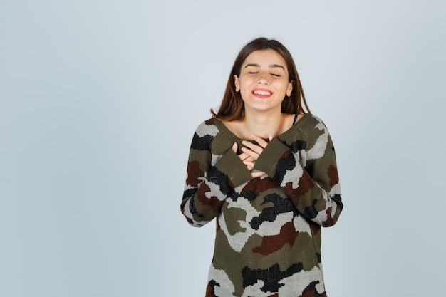 Giovane donna che tiene le mani sul petto in maglione, gonna e aspetto allegro
