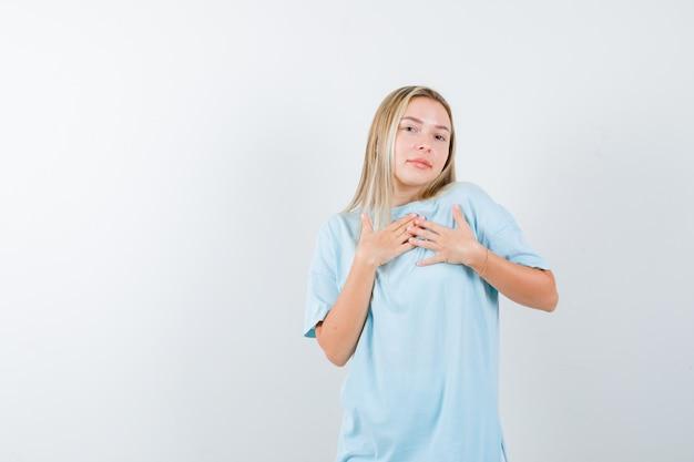 Giovane donna che tiene le mani sul petto in maglietta e sembra sicura. vista frontale.