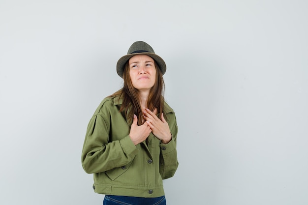 Young lady holding hands on chest while frowning in jacket pants hat