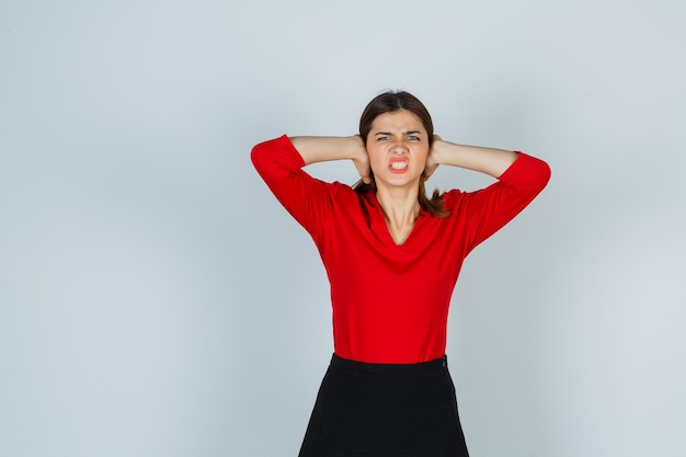 Giovane donna che tiene le mani sulle orecchie in camicetta rossa, gonna e sguardo infastidito