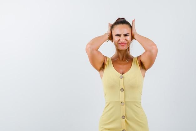 Giovane donna che tiene le mani sulle orecchie in abito giallo e guardando infastidito, vista frontale.