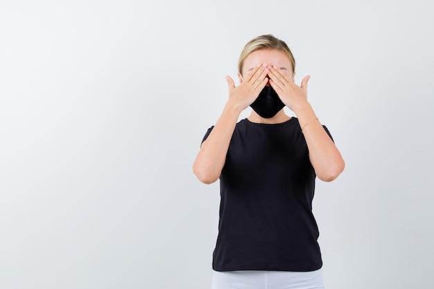 Giovane donna che si tiene per mano sugli occhi in maglietta, pantaloni, maschera medica e sembra seria