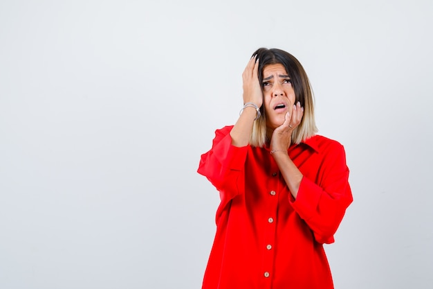 Young lady holding hands on face in red oversize shirt and looking anxious. front view.