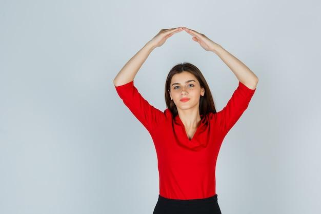 Giovane signora che tiene le mani sopra la testa come tetto di casa in camicetta rossa, gonna e aspetto carino