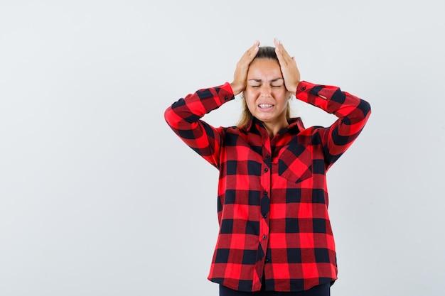Giovane signora che tiene le mani sulla testa in camicia casual e sembra infastidita. vista frontale.