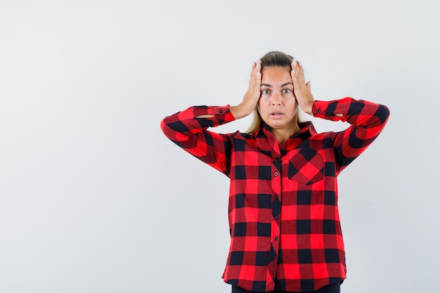 Young lady holding hands on head in checked shirt and looking wistful