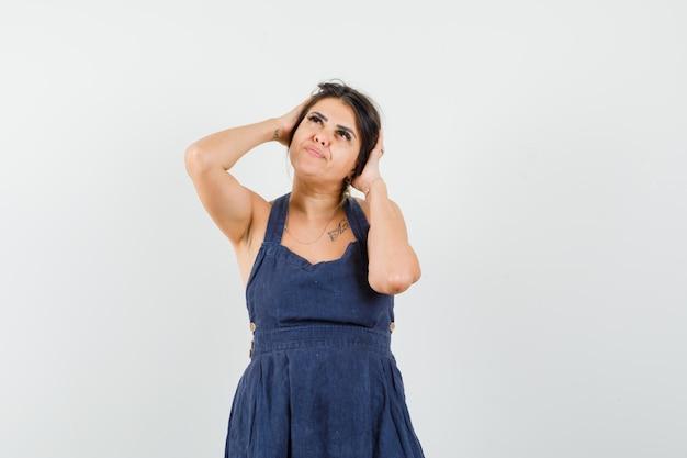 Giovane donna che si tiene per mano alla testa in abito e sembra pensierosa
