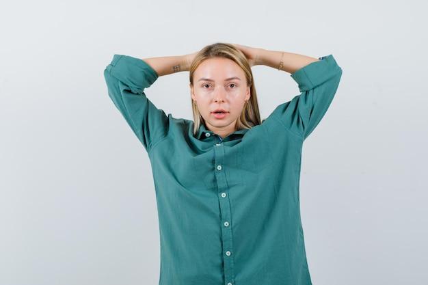 Giovane donna che si tiene per mano dietro la testa in camicia verde e sembra sicura