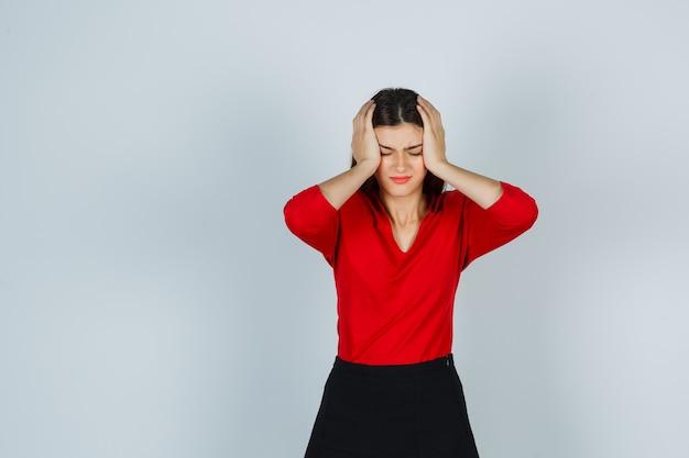 Giovane donna che tiene le mani sulla testa in camicetta rossa, gonna e sguardo infastidito