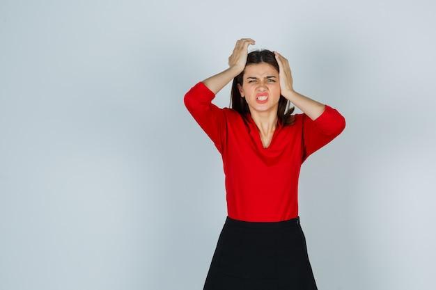 Giovane donna che tiene le mani sulla testa in camicetta rossa, gonna e sembra esausta