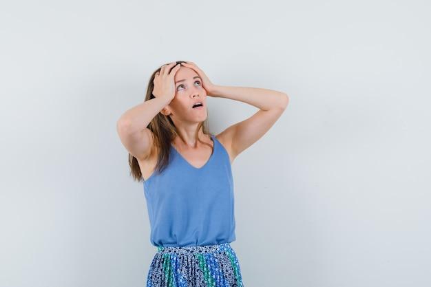 Giovane donna che tiene le mani sulla testa in canottiera, gonna e sembra impotente, vista frontale.