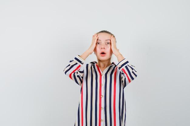 Giovane donna che si tiene per mano alla testa in camicia a righe e sembra turbata