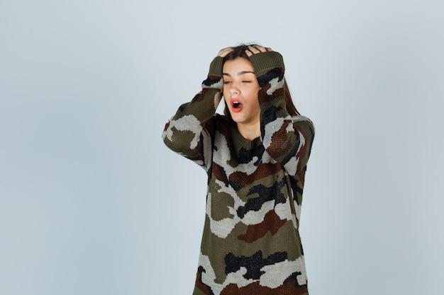 Giovane donna che tiene le mani sulla testa in maglione, gonna e guardando ansioso