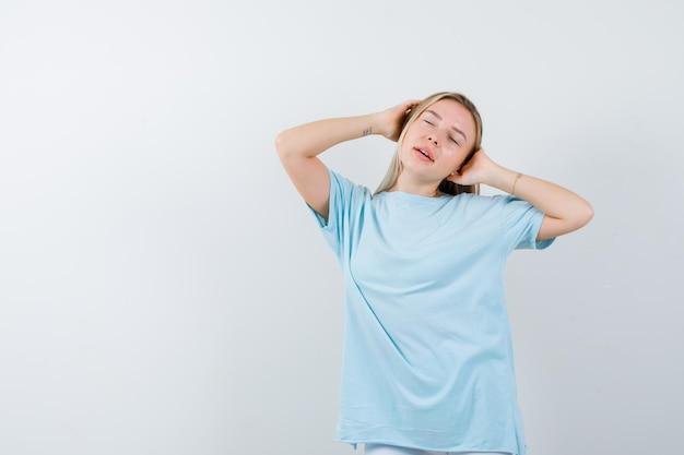 Giovane donna che si tiene per mano sulla testa in maglietta e sembra pacifica isolata