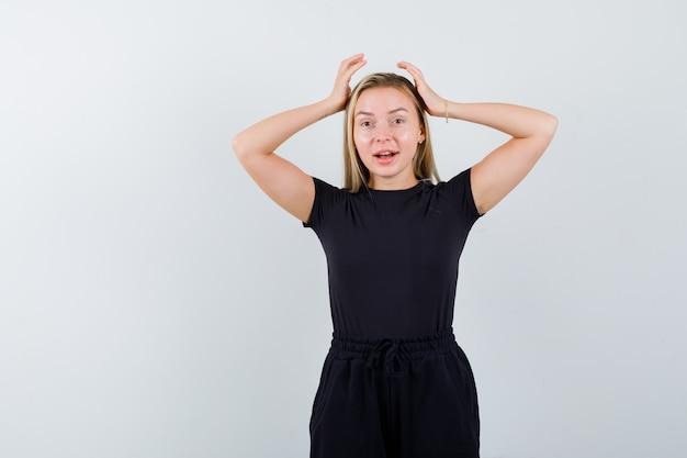 Giovane donna che tiene le mani sulla testa in maglietta, pantaloni e sembra gioiosa. vista frontale.