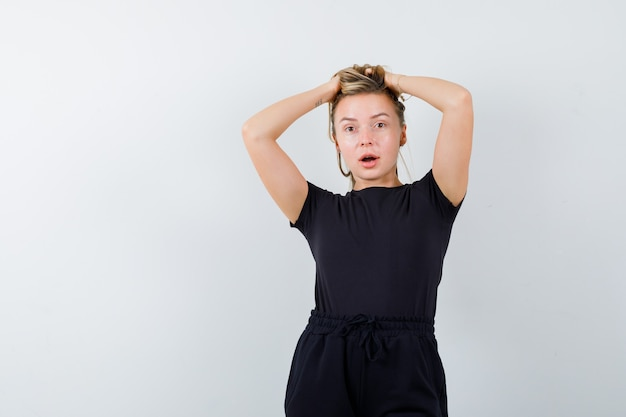 Young lady holding hands on head in t-shirt, pants and looking thoughtful. front view.