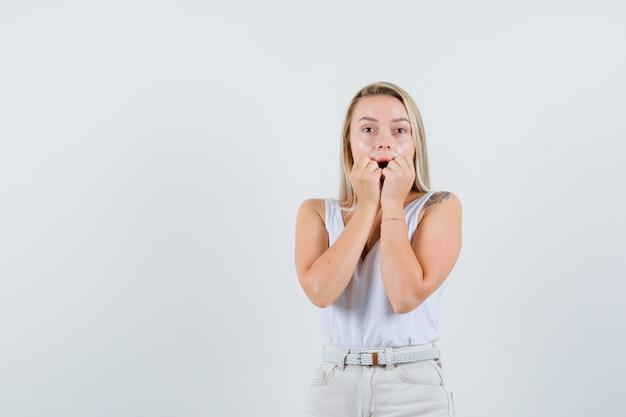 Giovane donna che tiene le mani sulla sua mascella caduta in camicetta bianca e cerca spazio libero emotivo per il tuo testo
