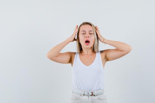 Giovane donna che tiene le mani sulla sua testa in camicetta bianca e sembra dolorosa