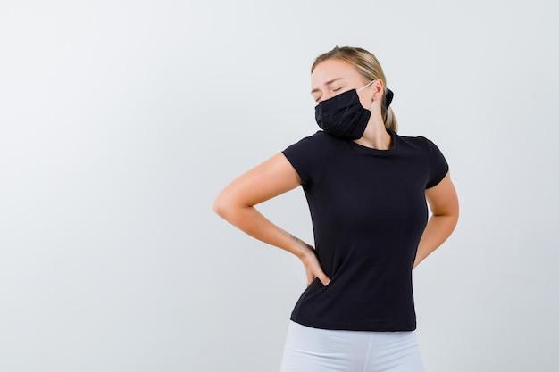 Giovane donna che si tiene per mano sull'anca in maglietta, pantaloni, maschera medica e sembra stanca