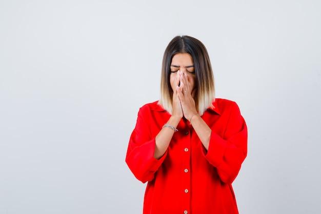 赤い特大のシャツで祈りのジェスチャーで手をつないで、希望に満ちた若い女性。正面図。