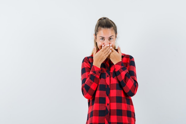 Young lady holding hands on mouth in checked shirt and looking cheery