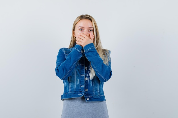 Giovane donna che si tiene per mano sulla bocca in maglietta, giacca di jeans, gonna e sembra stupita