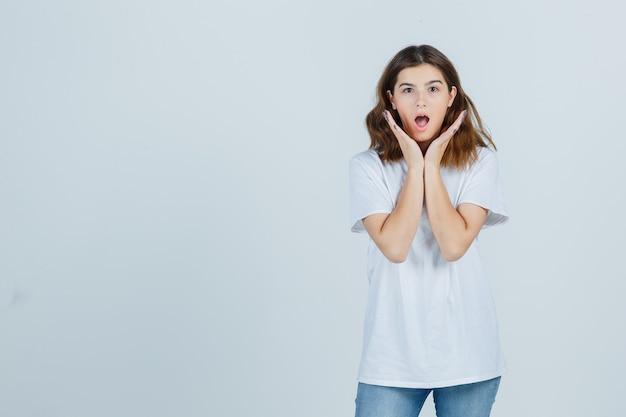 Tシャツ、ジーンズで頬の近くに手を握って、驚いて見える若い女性。正面図。