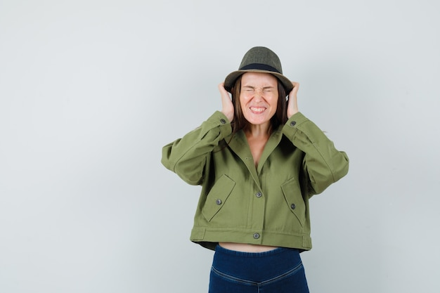 Young lady holding hands near ears in jacket pants hat and looking blissful