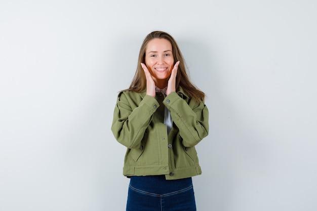 シャツ、ジャケットの顔の近くで手を握り、楽しい正面図を探している若い女性。