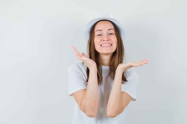 白いtシャツの帽子で顔の近くに手を握って、かわいく見える若い女性