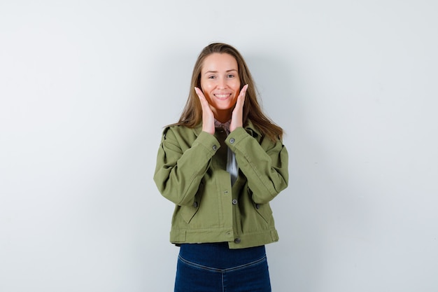 Young lady holding hands near face in shirt, jacket and looking delightful, front view.