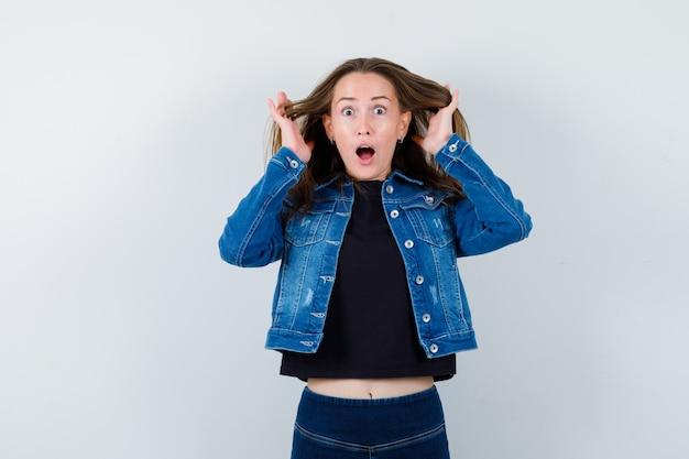 ブラウスを着て頭の近くで手をつないで、驚いて見える若い女性。正面図。