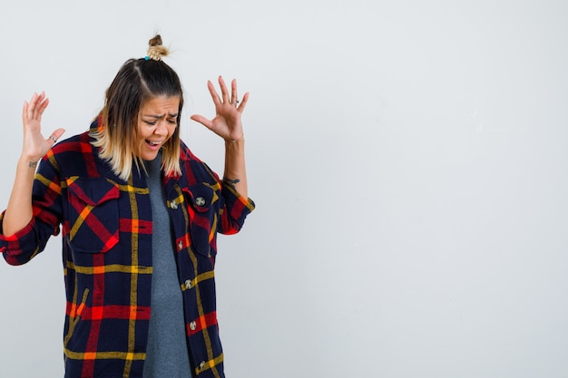 Young lady holding hands near head, standing sideways in casual checked shirt and looking disappointed .