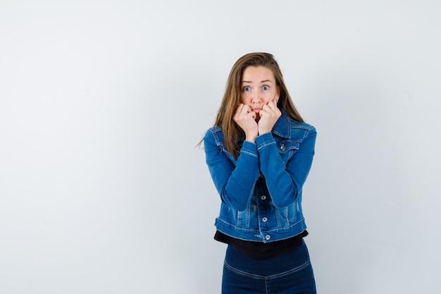ブラウス、ジャケット、怖い顔、正面図で口の近くで手を握っている若い女性。