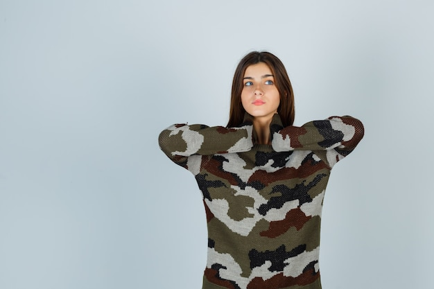 Young lady holding hands on neck in sweater and looking pensive