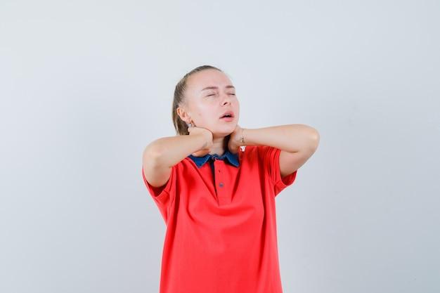 Giovane donna che tiene le mani sul collo in maglietta e sembra esausta