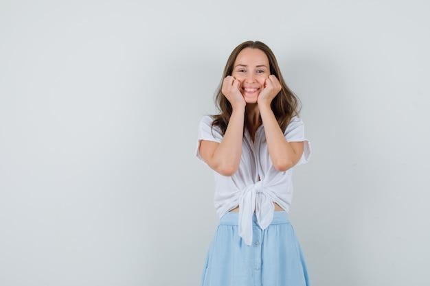 Молодая дама держится за щеки в блузке, юбке и прекрасно выглядит
