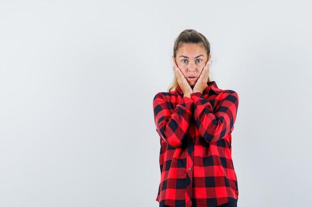 Молодая дама в клетчатой рубашке держит руки за щеки и выглядит встревоженной