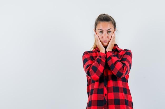 Молодая дама в клетчатой рубашке держит руки за щеки и выглядит нежной