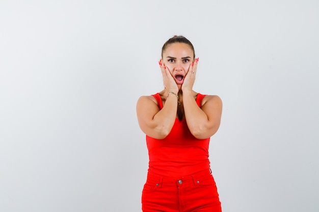 赤い一重項、赤いズボンで頬に手をつないで、困惑しているように見える若い女性、正面図。