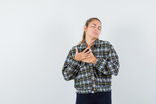 Молодая дама, взявшись за руки на груди в рубашке, шортах и выглядя мирно. передний план.