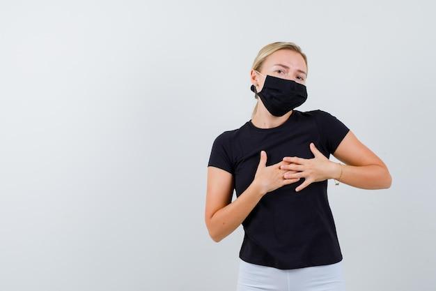 젊은 아가씨 티셔츠, 바지, 의료 마스크에 가슴에 손을 잡고 자신감을 찾고
