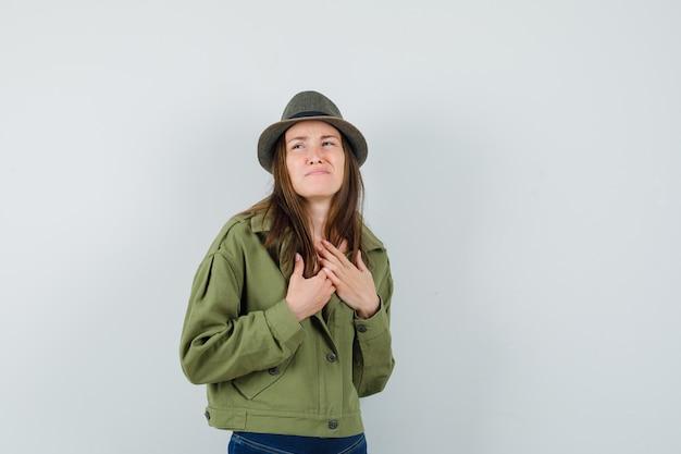ジャケットパンツ帽子で眉をひそめながら胸に手をつないで若い女性