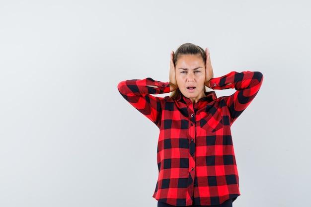 Девушка в клетчатой рубашке держит руки за уши и выглядит раздраженной