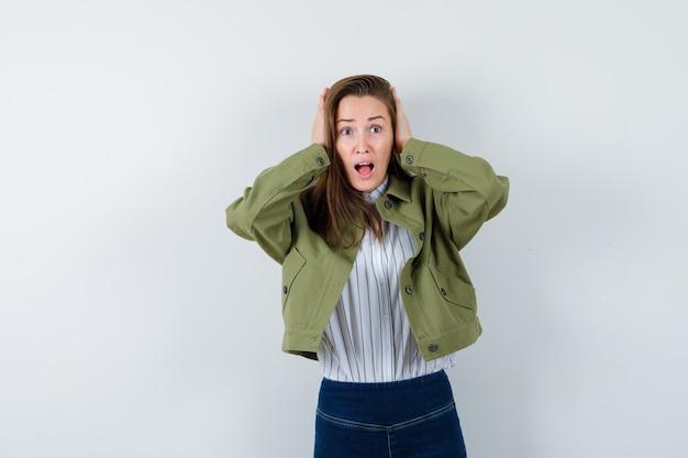 シャツ、ジャケットで耳に手をつないで、興奮している若い女性。正面図。