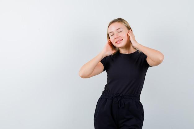 Tシャツ、ズボン、満足そうに見える、正面図で耳に手をつないでいる若い女性。